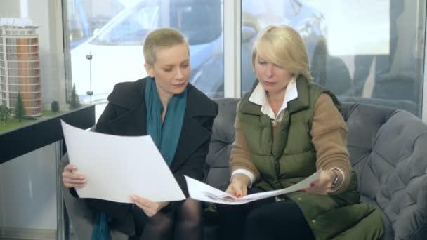 dvě ženy mluví, sedí v prodejní kanceláři na pozadí uspořádání budovy