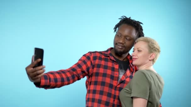 African guy and caucasian girl making selfie with smartphone. blue background.