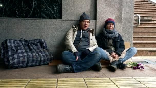 Obdachlose bitten um Almosen, sitzen auf dem Bürgersteig gegen die Wand