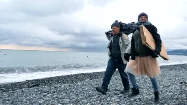 šťastný pár bezdomovců, muž a žena běží na pláži