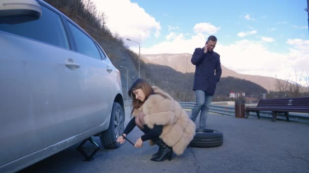 humor. woman changing a car wheel. man talking on the phone
