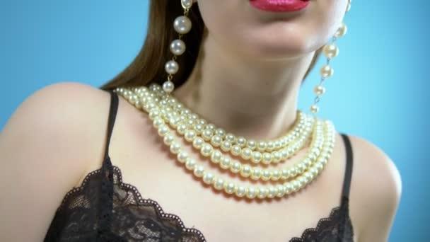 krásná mladá dívka s perlami a náušnicemi na modrém pozadí