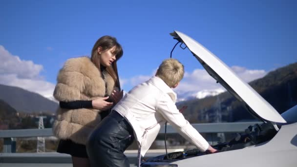 two girls are charging the battery in a car standing on the side of the road