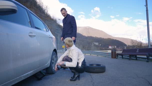 humor. woman changing a car wheel. a man rides past on electric skate Board.