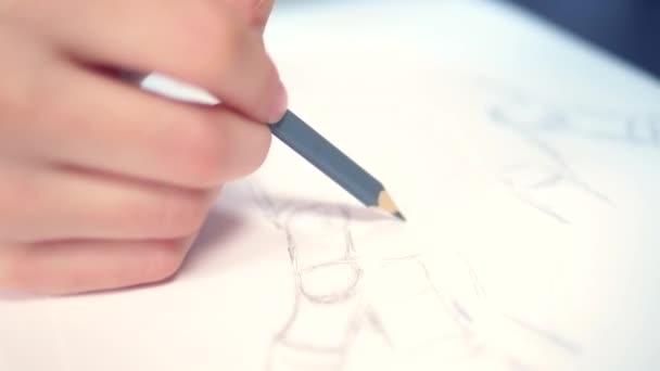 schöne brünette Mädchen zeichnet eine Skizze mit einer hölzernen Schaufensterpuppe