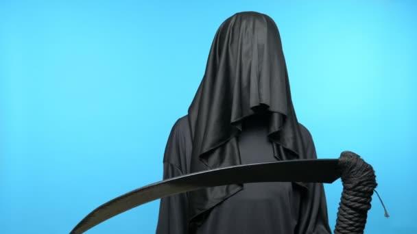 egy férfi fekete köpenyben, kapucnival, egy kasza kék háttérrel.