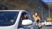 Két gyönyörű lány tolja a törött autót az úton. Egy férfi ül a volán mögött.