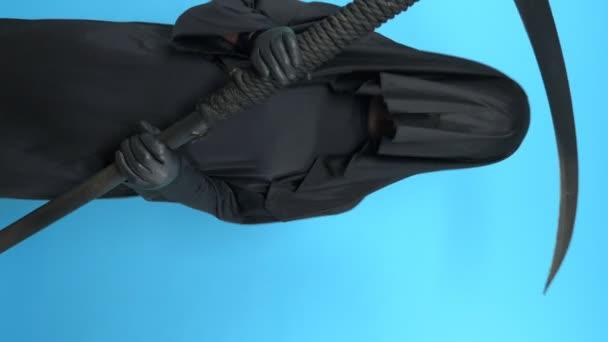 függőleges lövés. férfi egy halál öltöny egy kasza egy kék háttér tánc