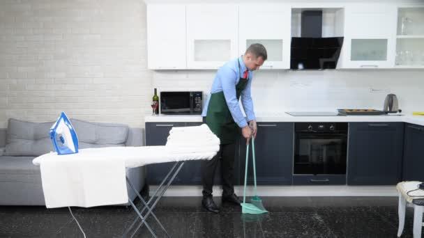 pohledný muž v kravatě a zástěře zametání podlahy v kuchyni