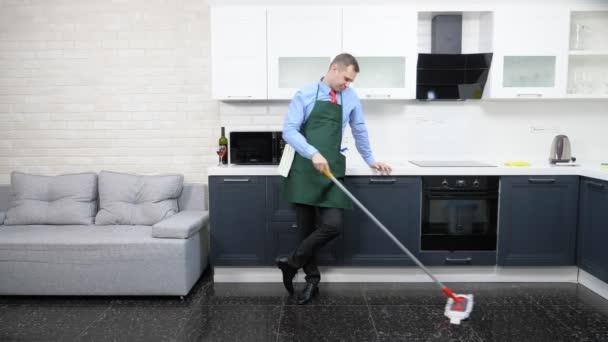 schöner Mann in Krawatte und Schürze wischt den Boden in der Küche