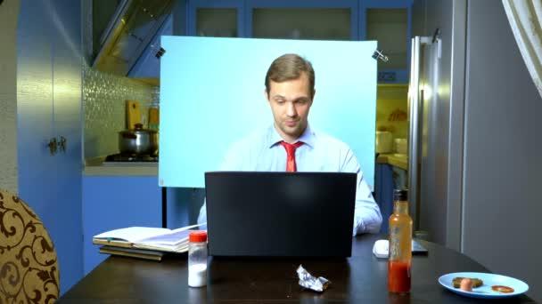muž pořádá videokonferenci doma v kuchyni, jeho žena jí u stolu
