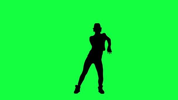 Siluetta di una ragazza con il cappello di danza come il re del pop. Priorità bassa chiave di crominanza. Silhouette di una donna che balla su uno sfondo verde