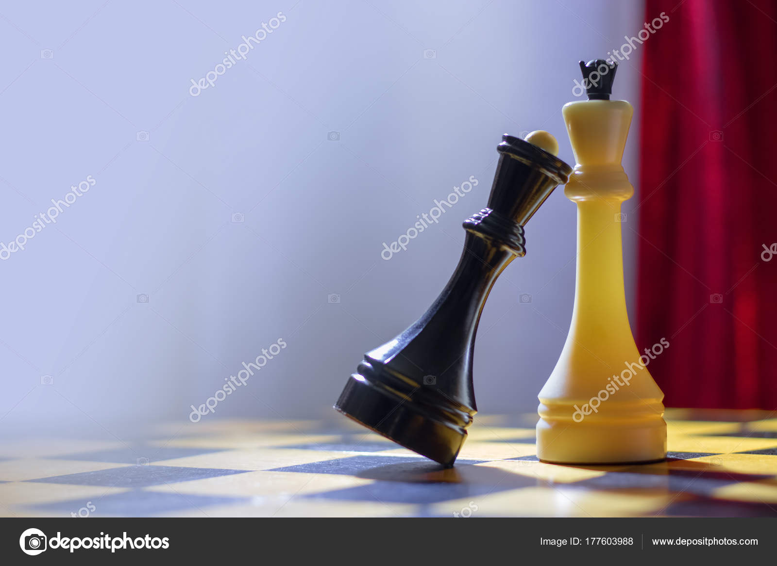 Chess black queen and white king stand on a chessboard stock photo