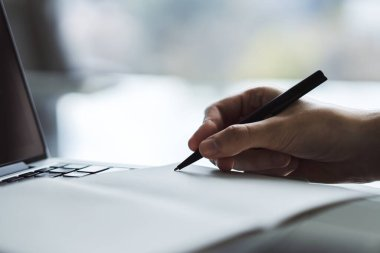 Man writes with a pen in notebook on laptop keyboard in a sunny office, business and education concept. Close up