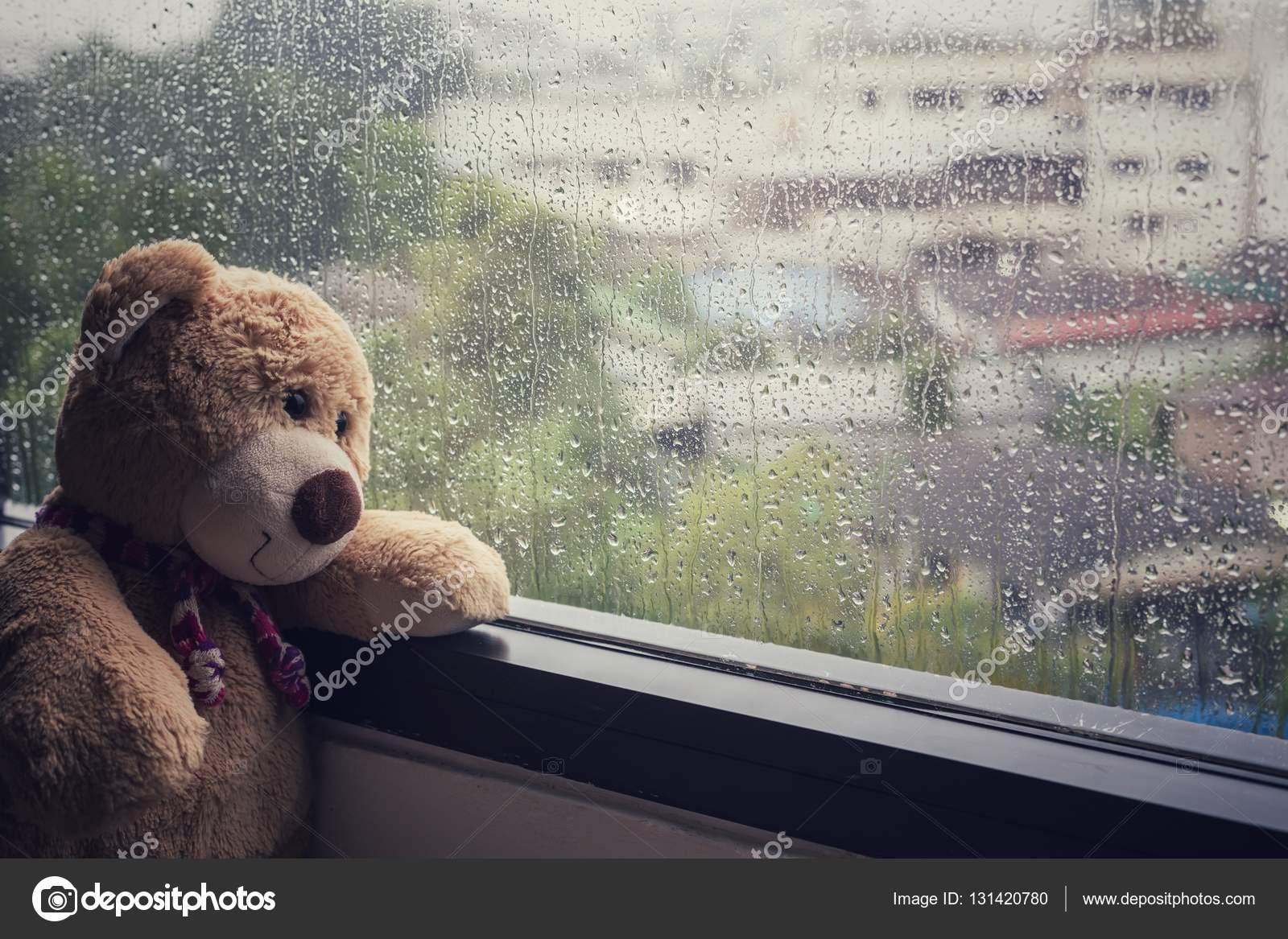 Teddy bear sitting beside the window while raining — Stock Photo ©  PhanuwatNandee #131420780