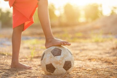 Young Asian boy playing old and dirty classic soccer ball in the