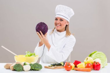 Female chef showing cabbage while making healthy meal