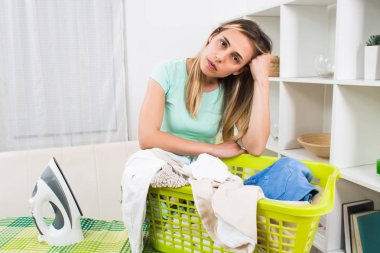Woman is displeased because she has got to much laundry for ironing.