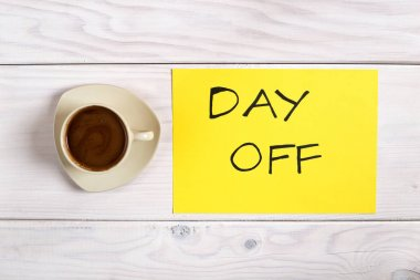 Coffee cup and text  day off on wooden table.Image is intentionally toned. stock vector