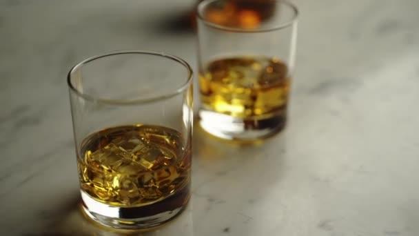 Szemüveg ízletes eredeti scotch whisky jégkockákkal a márvány asztalon, borostyán brabdy ünneplés és pihenés kocsmában vagy bárban. Arany whiskey ital, 4K-s slider.