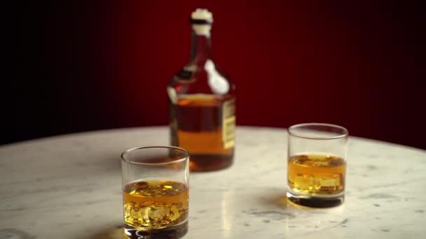 Zlatý originální whisky nápoj s kostkami ledu v křišťálově čistých sklenicích na mramorovém stole, oslavou nočního života a alkoholickým odpočinkem. Zlatý koňak ve skle, jezdec ve 4K