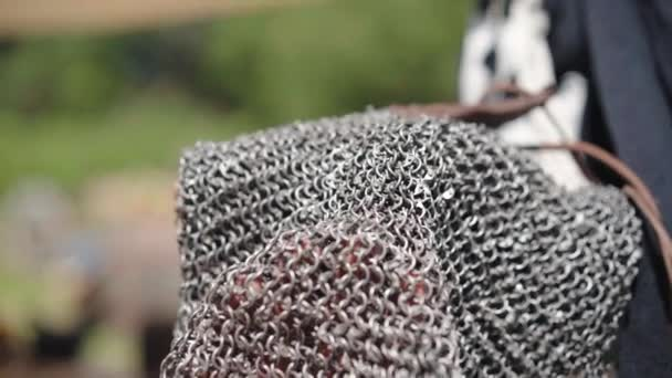 Medieval knight wearing traditional steel chain armor and holding sword with cross sign. Close up of a warrior in chainmail armor, medieval vendor selling warlike costume on marketplace