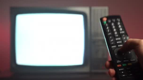 Közelkép az emberek kéz gazdaság vintage TV távirányító és nyomógombok váltani TV csatorna