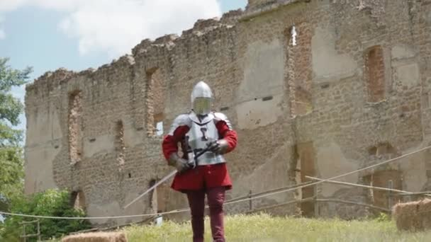 Medieval knight dressed in traditional heavy armor and holding metal sword walking on the background of ancient castle. Armed knight is ready for battle on the field with enemies. Medieval knight and