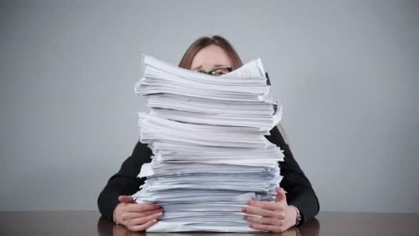 Stack of unfinished paperwork laying at the table in the office room, female accountant sitting behind the documents and files and feeling streesed from routine office work. Financial calculations