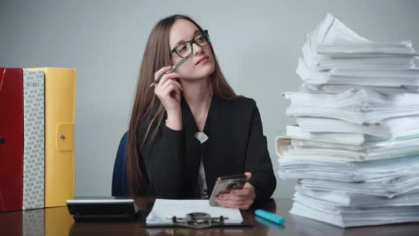 Young pretty office worker sitting at the table, looking at the stack of documents and paperworks