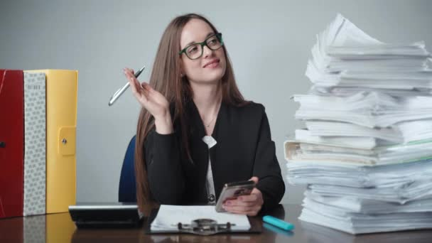 Pretty smiling office worker dreaming in the office after hard working day. Young manager having break, using smartphone for calculating. Stacks of paperwork and deadline concept