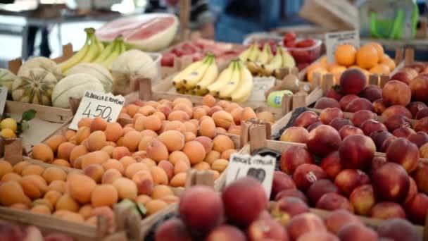 Ökológiai gyümölcsök a mezőgazdasági termelők piacán, friss trópusi gyümölcsök választéka a piac pultjánál lévő fa kosarakban. Táplálkozás és egészséges táplálkozás