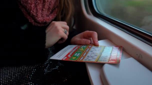 ROME, OLASZORSZÁG - JANUÁR 2020: Női utas utazik vonattal Rómába, és karcolás lottó azonnali nyeremény jegyet az ablak közelében. Lottó játék koncepció