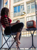 Beautiful young woman in the home clothes sitting on a chair on the balcony and watching a TV