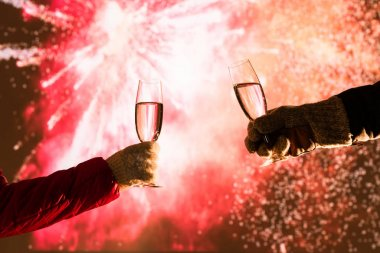 Merry man and woman toasting with glasses champagne celebrate holiday christmas or new year during celebratory fireworks on the  night sky.