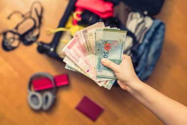 Female hands with Asian money and suitcase with things on the floor.Travel concept