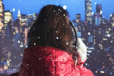 Young woman in a winter jacket and knitted gloves listening music in the headphones on roof of building of night New York at snowfall. Aerial and panorama view of skyscrapers of New York City. Midtown of Manhattan at Christmas time