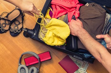 A man packing a suitcase or luggage for travel. Concept