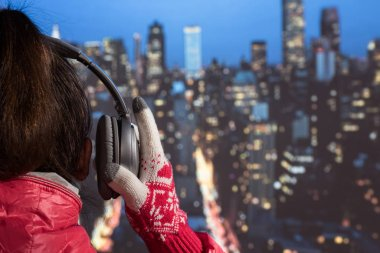 young woman in a winter jacket and knitted gloves listening music in the headphones on the roof against the backdrop of night New York. Aerial and panorama view of skyscrapers of New York City. Top view of midtown of Manhattan.