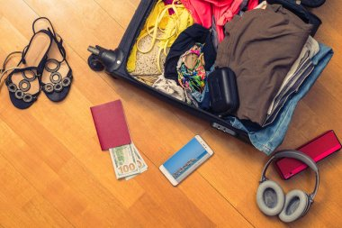 A suitcase with things and a foreign passport. Asian money and hundred-dollar bills for travel. Concept