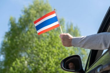 Man holding Thailand flag from the open car window. Concept
