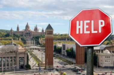 Help stop sign with view of Spain square in Barcelona, Spain. Humanitarian and economic help during economic crisis and coronavirus pandemic. Help for local business