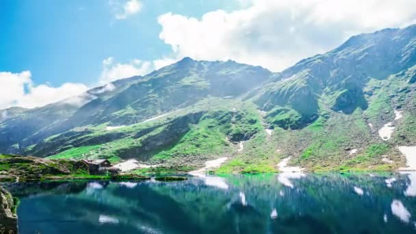 Fascinating time lapse video of majestic clouds in mountains with snow, in the lake reflecting the mountains with snow. Alone house stay near lake. And cute sun shines with game of clouds.