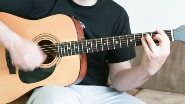 Egy fickó akusztikus hathúros gitáron játszik. megtanulnak játszani egy hangszeren közelkép.