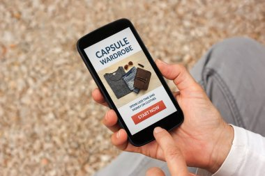 Hands holding smart phone with capsule wardrobe concept on screen