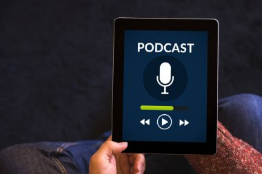Hands holding tablet with podcast concept on screen