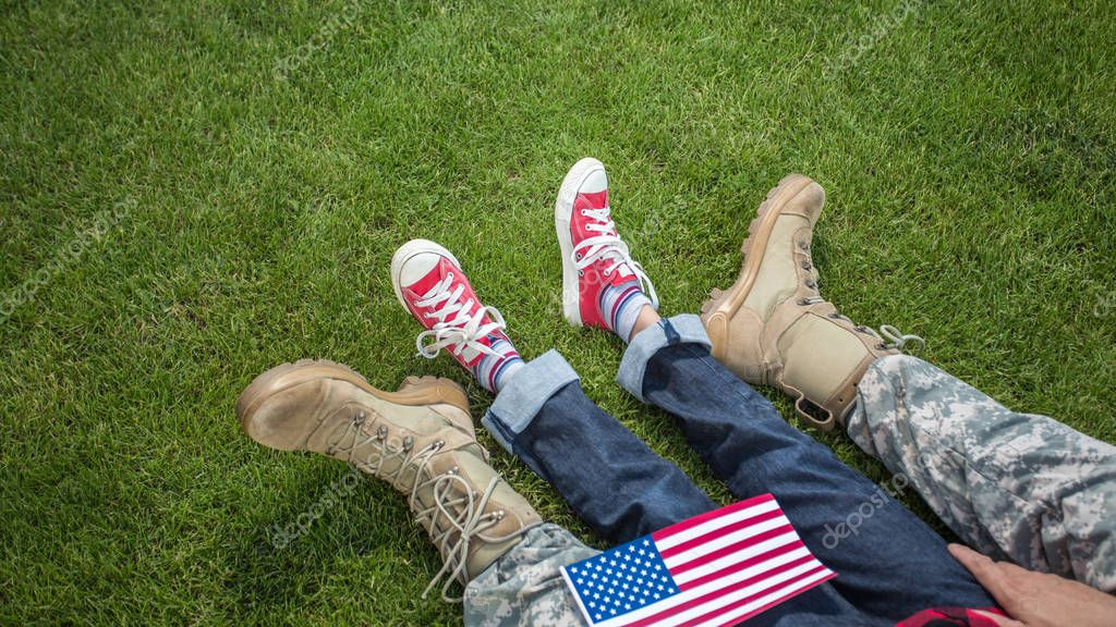 Father and son legs on green grass