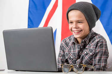 Boy studing in front of laptop with english flag on the background