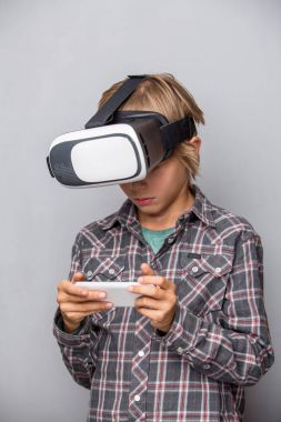 Boy in virtual reality glasses holdnig cell phone
