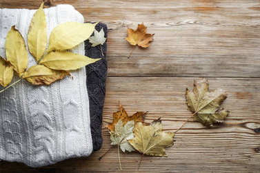 Pile of knitted winter  or autumn clothes on wooden background